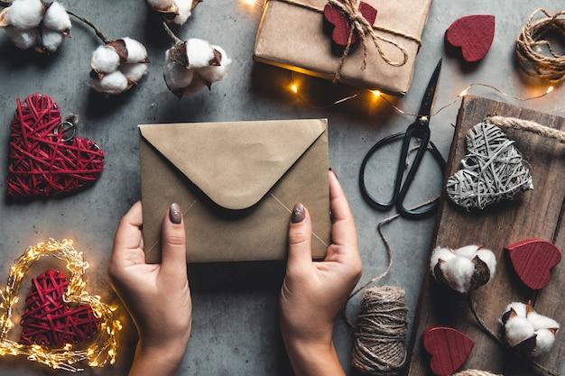 Sfondo di san valentino, carta di san valentino con fiori di cotone e regali su sfondo grigio