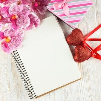 Fondo di giorno di biglietti di s. valentino con il blocco note vuoto per testo, giftbox, fiore rosa dell'orchidea e cuori su superficie di legno bianca. vista piana laico e dall'alto.