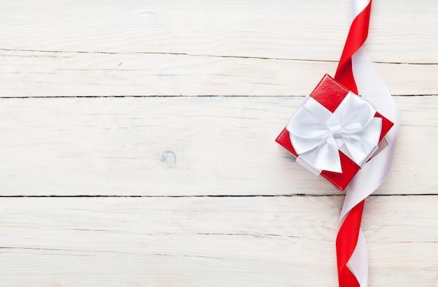 Sfondo di san valentino con confezione regalo su sfondo bianco tavolo in legno