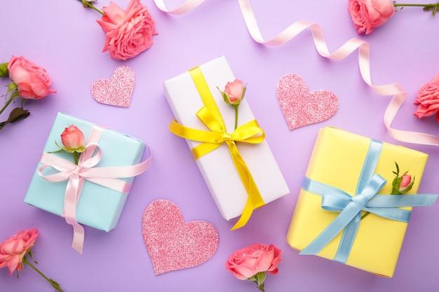 Sfondo di san valentino con rose rosa e confezione regalo su sfondo viola. vista dall'alto con copia spazio.
