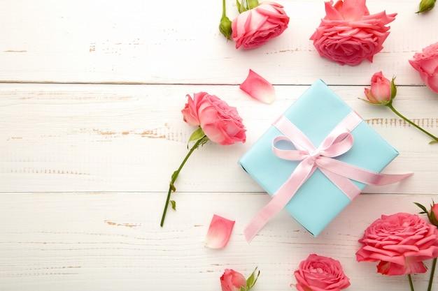 Sfondo di san valentino con rose rosa e confezione regalo sul tavolo bianco. vista dall'alto con copia spazio