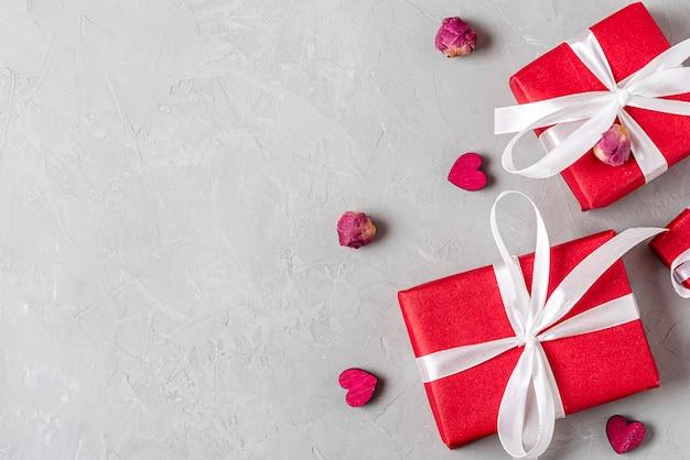Sfondo di san valentino con scatole regalo rosse, cuori di legno e boccioli di fiori di peonia essiccati su sfondo grigio cemento. vista dall'alto con copia spazio