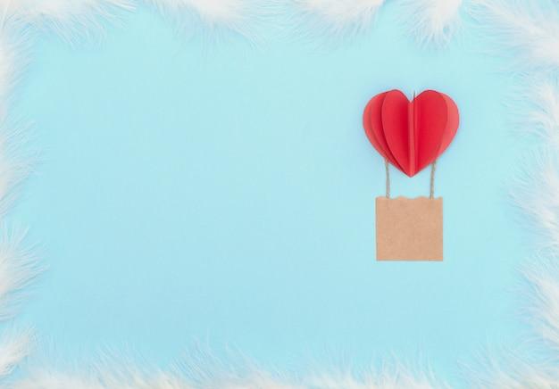Sfondo di san valentino con palloncino cuore rosso con cesto e piume bianche