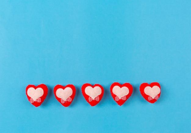 Fondo di giorno di biglietti di s. valentino con cuore rosso e contenitore di regalo su fondo blu.