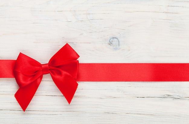 Sfondo di san valentino con nastro rosso su legno bianco