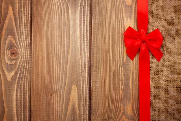 Sfondo di san valentino con nastro rosso su legno e tela