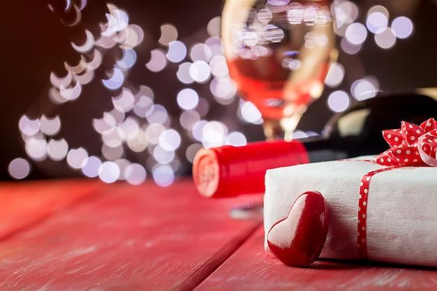 Sfondo di san valentino con vino rosso, bicchiere di vino e confezione regalo