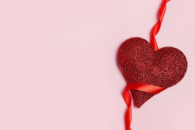 Carta di san valentino con cuore rosso e nastro su sfondo rosa. copia spazio