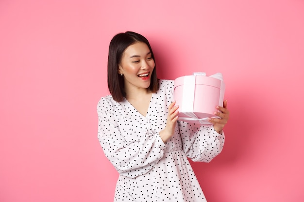 San valentino, concetto di celebrazione. bella donna asiatica che tiene confezione regalo romantica, sorridendo felice, in piedi sopra il rosa