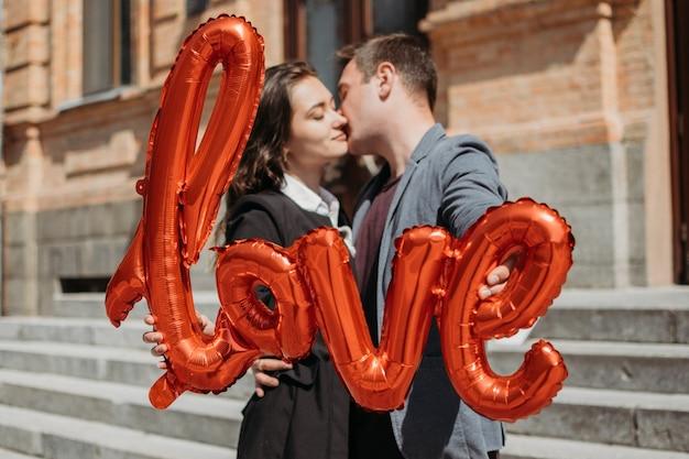 Celebrazione di san valentino e concetto di incontri. felice coppia di innamorati con palloncini rossi d'amore nella strada della città. ritratto all'aperto di giovane coppia con palloncino a forma di parola amore.
