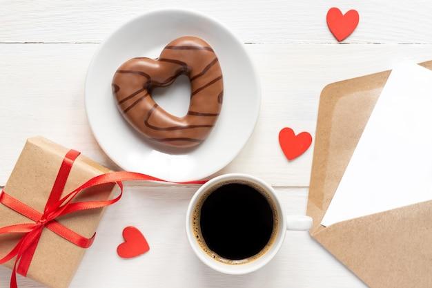 San valentino. caffè, biscotto al cioccolato a forma di cuore, confezione regalo e carta di carta con busta artigianale sulla vista dall'alto del tavolo in legno. stile piatto.