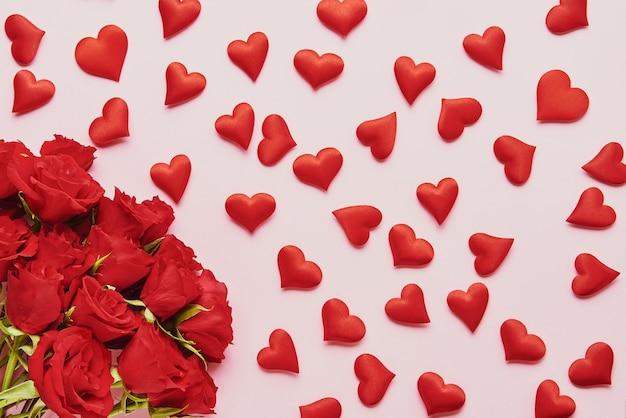 Concetto di san valentino. cuori rossi e bouquet di fiori di rose rosse su sfondo rosa. lay piatto