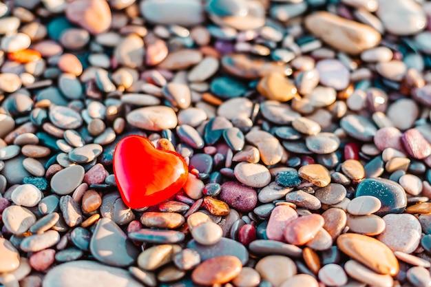 Concetto di san valentino. simbolo di amore romantico del cuore rosso sulla spiaggia di ciottoli con spazio di copia. modello per composizioni ispiratrici e cartoline di citazione.