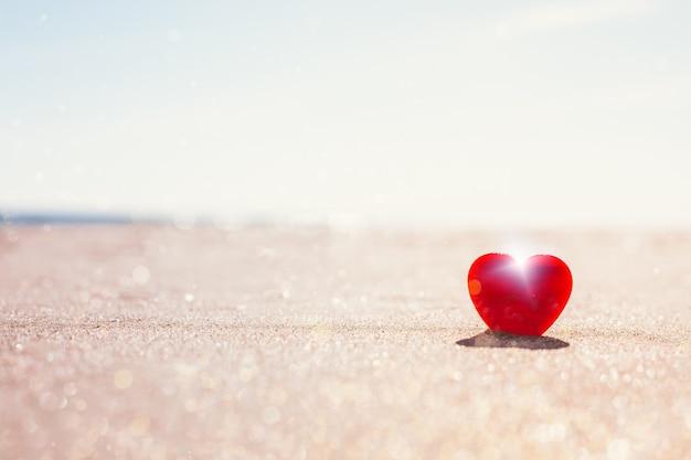 Concetto di san valentino. simbolo di amore romantico del cuore rosso sulla spiaggia di sabbia con lo spazio della copia.