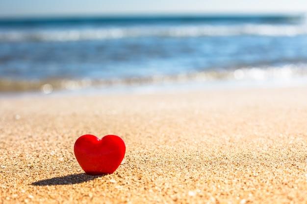 Concetto di giorno di biglietti di s. valentino simbolo di amore romantico del cuore rosso sulla spiaggia di sabbia