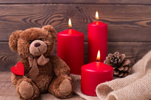Concetto di giorno di san valentino orsacchiotto mantiene le candele del cuore e un bernoccolo su fondo in legno messa a fuoco selettiva
