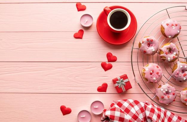 San valentino concetto. il giorno di san valentino brackfast con caffè e ciambelle isolati su fondo di legno rosa