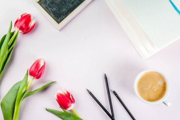 San valentino per le congratulazioni, biglietti di auguri. i tulipani freschi della molla fiorisce con il blocco note, tazza da caffè, su una vista superiore bianca