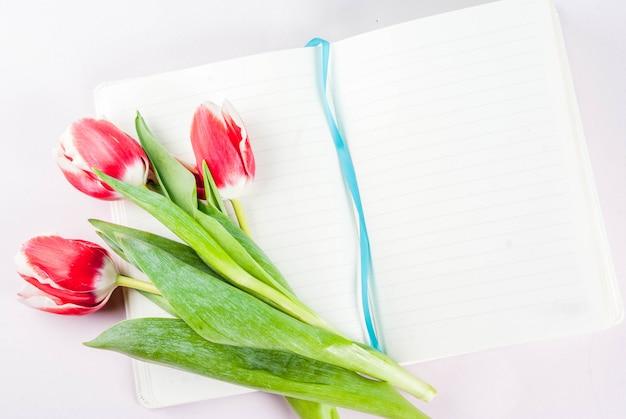 San valentino per le congratulazioni, biglietti di auguri. i tulipani freschi della molla fiorisce con il blocco note su una vista superiore bianca