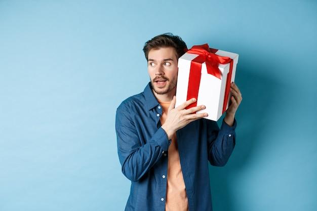 San valentino. ragazzo curioso che tiene confezione regalo vicino all'orecchio, cercando di indovinare cosa c'è dentro sorpresa presente, in piedi su sfondo blu.