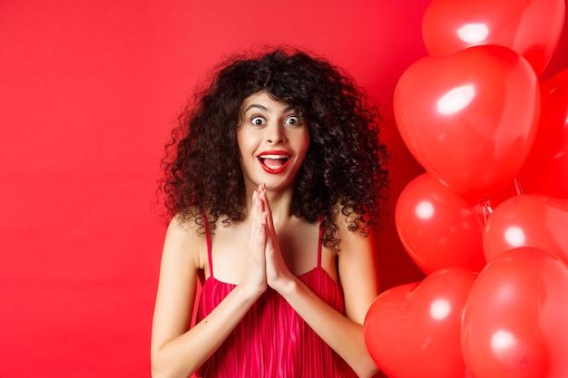 San valentino. eccitata donna caucasica in abito che salta dallo stupore, guardando qualcosa di provocante, vuole ottenere un prodotto, in piedi vicino a palloncini cuori, sfondo bianco.