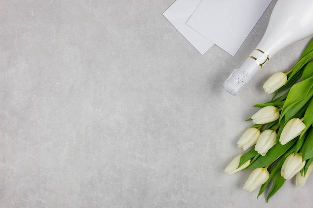 Il giorno di san valentino giaceva piatto con champagne, busta bianca e bouquet di fiori di tulipani bianchi su cemento leggero.
