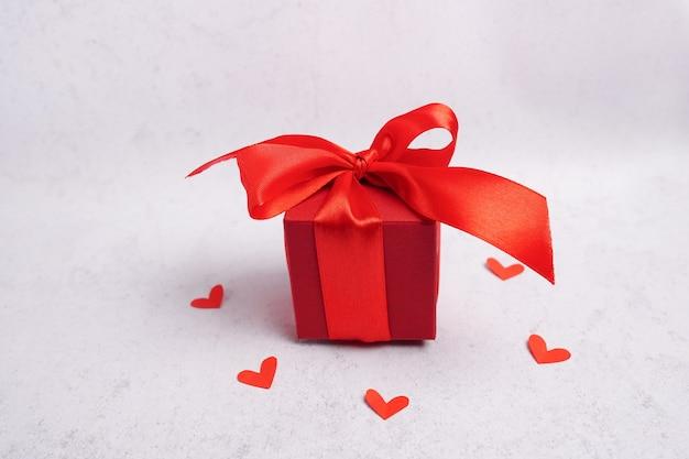 Confezione regalo di san valentino, cuori e nastro su sfondo grigio