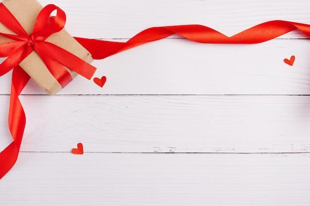 Confezione regalo di san valentino, cuori e nastro su fondo di legno bianco, spazio della copia
