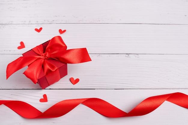 Contenitore di regalo, cuori e nastro di giorno di biglietti di s. valentino su fondo di legno bianco.