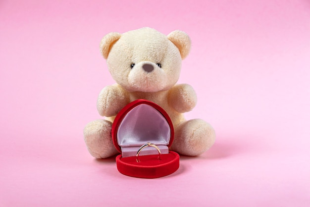 Regalo di san valentino. orsetto di peluche e portagioie a forma di cuore con anello in oro con diamanti sul muro rosa. concetto di proposta di matrimonio.