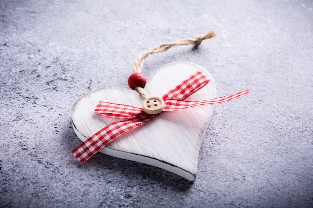 Cartolina d'auguri di san valentino con cuore in legno decorativo su pietra di cemento con spazio di copia per testo. concetto di san valentino. vista dall'alto