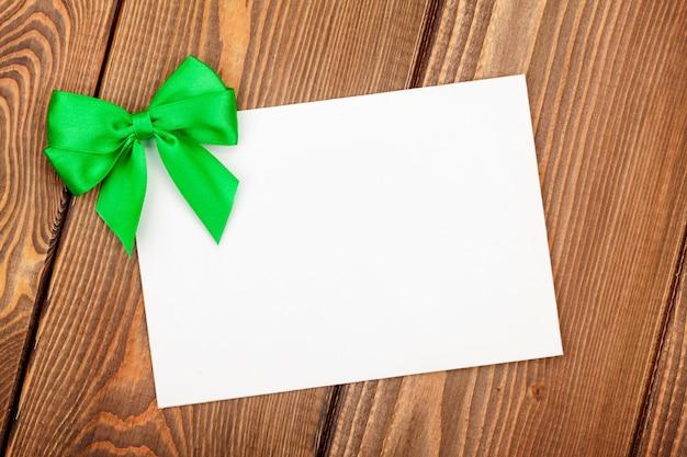 Biglietto di auguri di san valentino con fiocco verde su fondo in legno