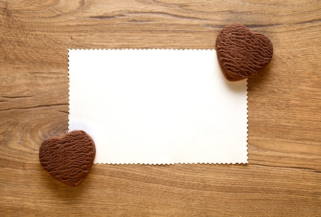 Cartolina d'auguri di san valentino con due biscotti al cioccolato a forma di cuore al forno su fondo di legno. vista dall'alto, spazio vuoto per il testo. lay piatto