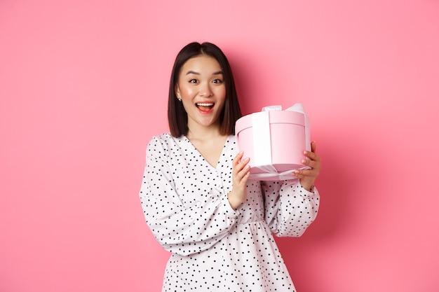 San valentino. felice donna asiatica che riceve un regalo in una scatola carina, sorridendo eccitata e grata, in piedi in abito contro il rosa
