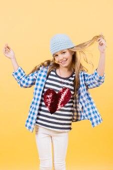 San valentino, celebrazione delle vacanze. sorriso della bambina con cuore rosso sulla maglietta, moda. bambino felice che sorride con lunghi capelli biondi, bellezza. moda bambino, bellezza, stile. amore, tendenza pastello incisiva