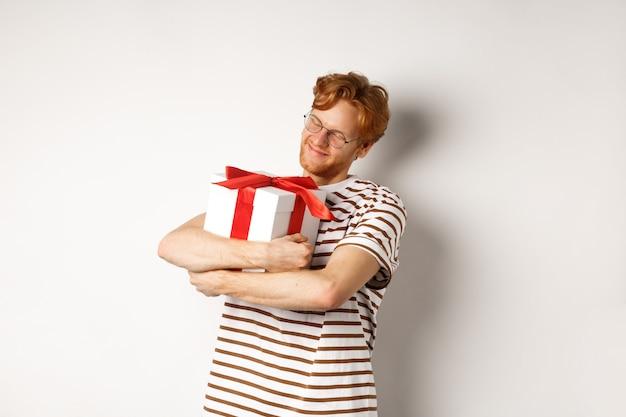 Il giorno di san valentino e il concetto di vacanze. uomo rosso felice che abbraccia la sua confezione regalo e sorridendo felice, in piedi su sfondo bianco.