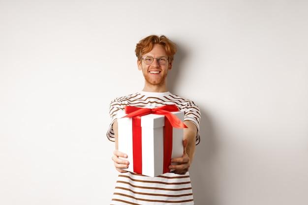 Il giorno di san valentino e il concetto di vacanze. felice redhead uomo sorridente e dandoti confezione regalo, congratulandosi con il compleanno, in piedi su sfondo bianco.