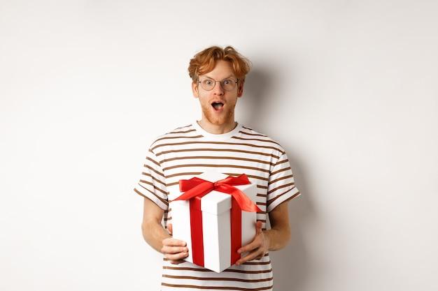 Il giorno di san valentino e il concetto di vacanze. fidanzato rosso sorpreso con gli occhiali guardando grato alla telecamera, riceve un grande regalo nella casella, in piedi su sfondo bianco.