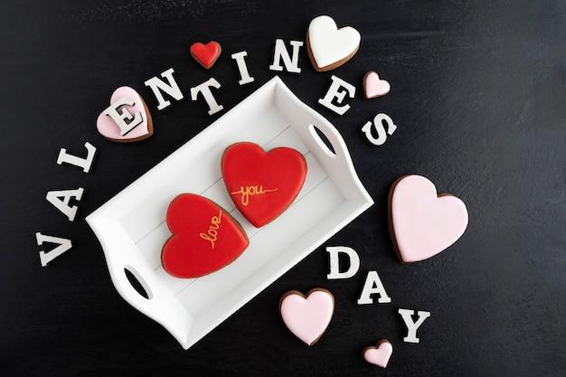 Iscrizione di san valentino da lettere e biscotti a forma di cuore allo zenzero su sfondo nero.