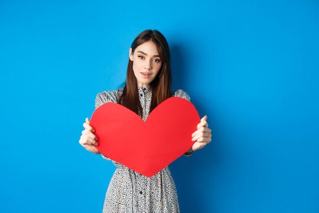 Il giorno di san valentino e il concetto di relazione. tenera giovane donna in abito allunga la mano e ti dà un grande cuore rosso, facendo confessione, in piedi romantico su sfondo blu