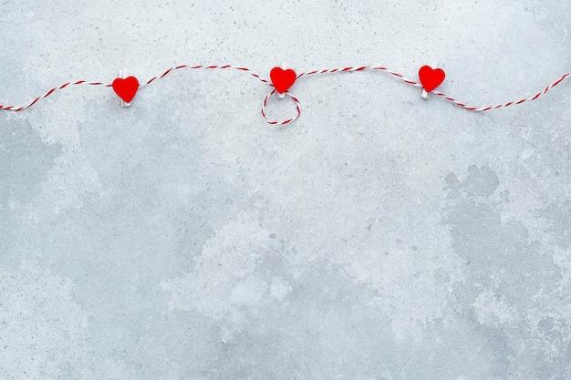 San valentino . nastro con cuori rossi o. posto per il testo su sfondo grigio muro. in modo piatto.