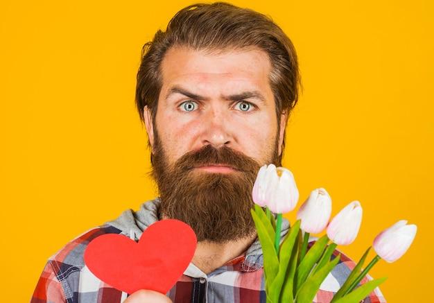 San valentino. uomo serio con cuore rosso e fiori.