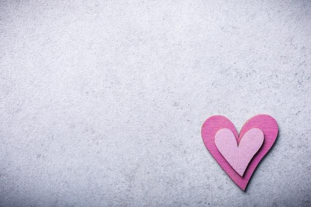 Superficie di san valentino con cuore in legno rosa decorativo su pietra di cemento con lo spazio della copia per testo. concetto di san valentino. vista dall'alto