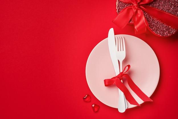 Tavolo o concetto di san valentino con piatto rosa vuoto e whiteware sul tavolo rosso o scarlatto. vista dall'alto laici piatta con copia spazio.