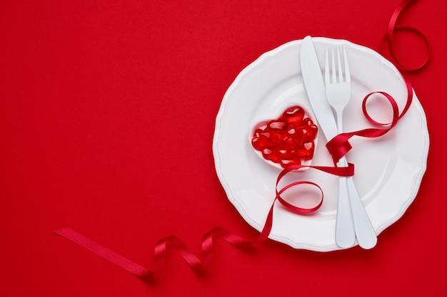 Tavola o concetto di giorno di biglietti di s. valentino con forchetta e coltello bianchi vuoti della coltelleria e del piatto con il nastro rosso sulla tabella scarlatta o rossa. concetto o vista dall'alto laici piana con lo spazio della copia.