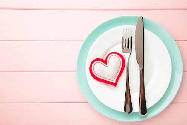 Regolazione di posto della tavola di giorno di biglietti di s. valentino sul rosa. sfondo di vacanze