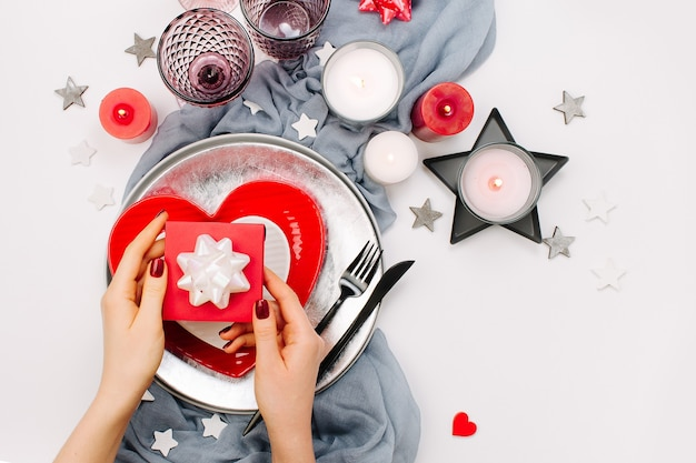 Regolazione della tavola di san valentino. le mani femminili tengono il regalo. piatti bianchi e rossi a forma di cuore, bicchieri per bevande, candele e posate sfondo bianco. concetto romantico