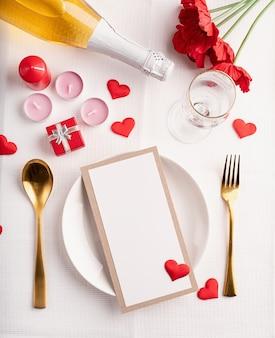 Regolazione della tavola di san valentino con menu, piatto, bottiglia di champagne vista dall'alto, mock up design