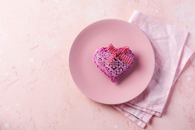 Regolazione della tavola di giorno di biglietti di s. valentino con il cuore rosa del regalo e del piatto su fondo leggero rosa