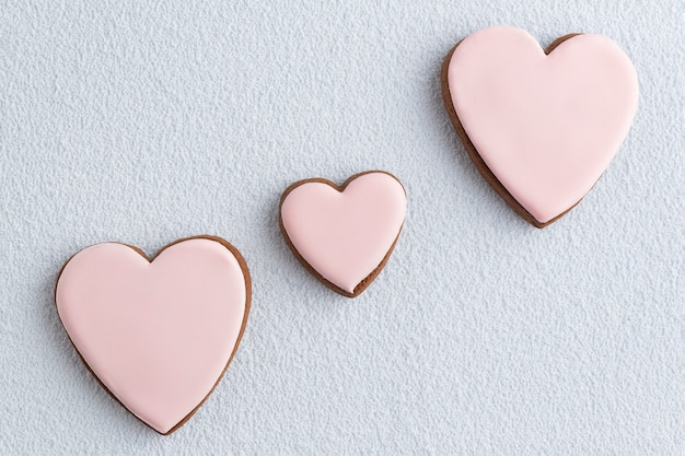 San valentino trattare. biscotti fatti in casa a forma di cuore allo zenzero con zucchero a velo su sfondo bianco